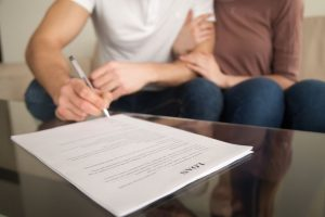 Man signs a contract with a woman holding his arm