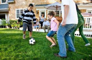 family plays soccer in their backyard
