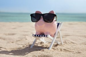 Piggy bank on the beach wearing sunglasses