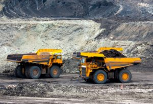 Two large yellow coal trucks in a strip mine