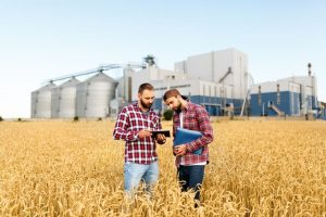 Two men stand in a wheat field looking at an ipad in front of a large warehouse