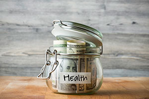 Mason jar labelled health with a hundred dollar bill in it