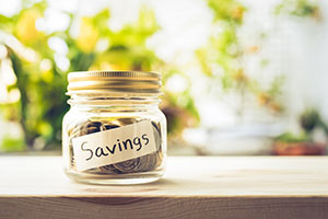 mason jar labelled savings with coins in it